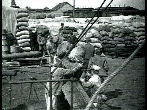vídeos y material grabado en eventos de stock de men unloading supplies from steam boat in harbor, passengers embarking onto boat / solovetsky island, russia - 1928