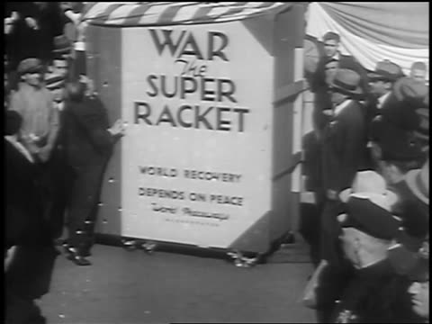 B/W 1933 men unveiling huge book entitled War the Super Racket as crowd watches / Union Square NY