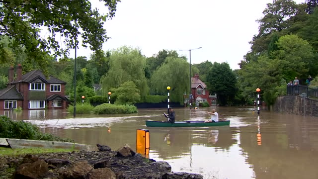 men use canoe to get about after flood water blocks road in north england - nautical vessel stock videos & royalty-free footage