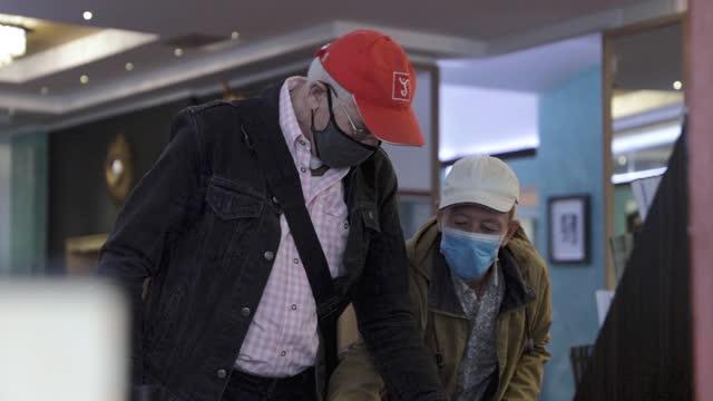 men using hand sanitizer in hotel foyer - cap stock videos & royalty-free footage