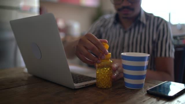 自宅でラップトップを使用し、鼻を吹き、薬を服用している男性 - ビタミン類点の映像素材/bロール