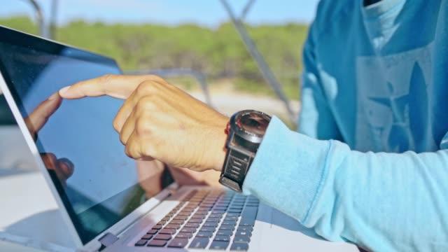 4K Men using laptop on sunny sailboat, real time