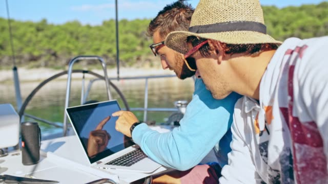 4k men using laptop on sunny sailboat, real time - sailor stock videos & royalty-free footage