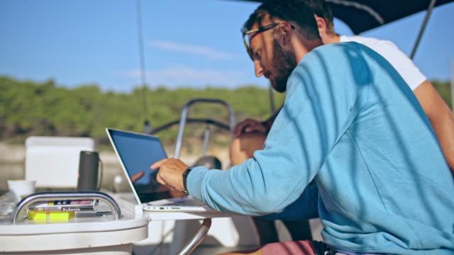 4k men using laptop on sunny sailboat, real time - barca da diporto video stock e b–roll