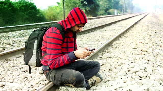 Men using Smart Phone near Railway Track