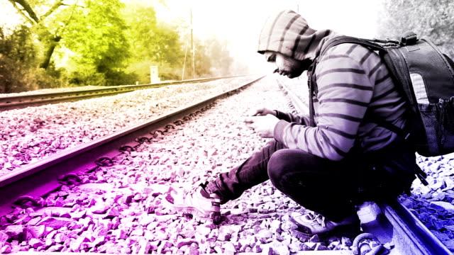 vídeos y material grabado en eventos de stock de hombres usando teléfono inteligente cerca de vías de ferrocarril - t mobile