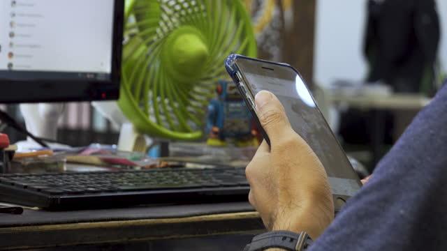 vidéos et rushes de hommes utilisant des smartphones. il était assis sur son téléphone lors de la détente sur le bureau à la maison - photo messaging