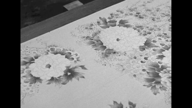 men using stencil and applying ink to length of silk spread out on long table / closer shot / cu stencil being lifted off silk to reveal floral... - 1930 stock videos & royalty-free footage