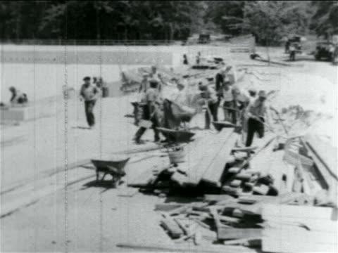 b/w 1934 men using wheelbarrows in wpa reservoir construction project / atlantic city nj / doc - 雇用促進局点の映像素材/bロール