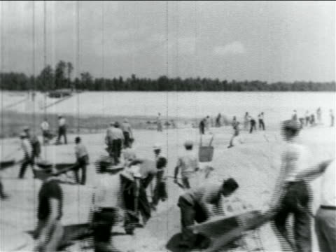 b/w 1934 men using wheelbarrows on wpa reservoir construction project / atlantic city nj / doc - 雇用促進局点の映像素材/bロール