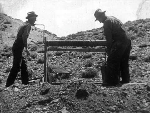 B/W 1927 men using winch to raise bucket from well / they pour rocks from bucket / gold mining