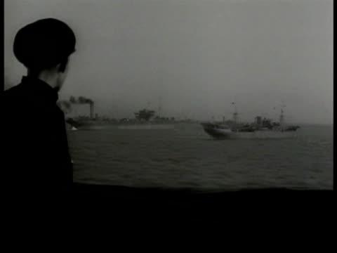 Men w/ helmets digging through rubble destroyed building Sailor watching fleet of battleships from deck Battleships at sea stern of ship FG MS...