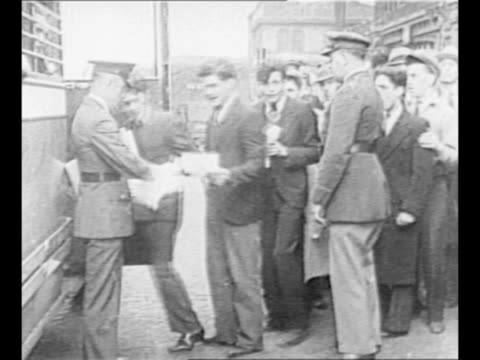 men wait in line on both sides of doorway to enter building as others exit / line of young men boards bus to travel to civilian conservation corps... - new deal video stock e b–roll