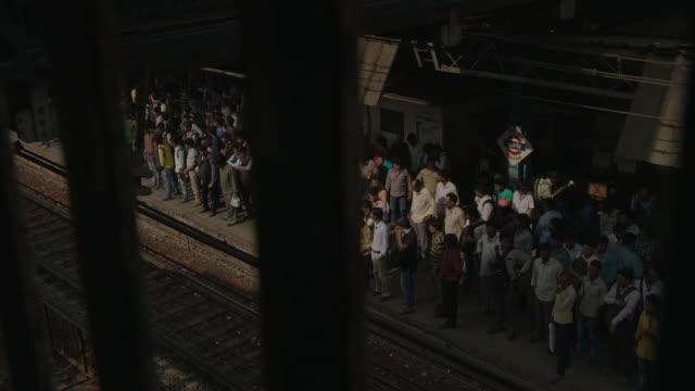 Men wait on the busy Wadala Road Station platform as an announcement is made, Wadala East, Mumbai, Maharashtra, India.