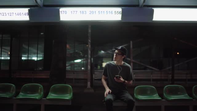vidéos et rushes de hommes attendant l'abri aux arrêts d'autobus à la nuit seulement - banc