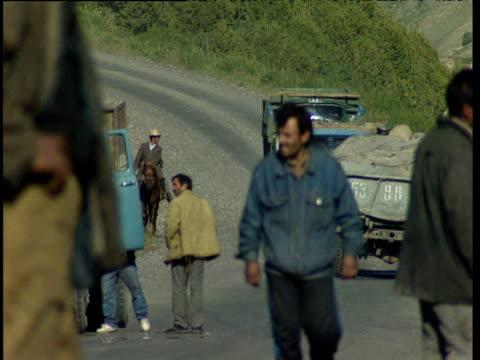 men walk along rural road as large trucks join queue of stationary vehicles tajikistan - ムラがある点の映像素材/bロール