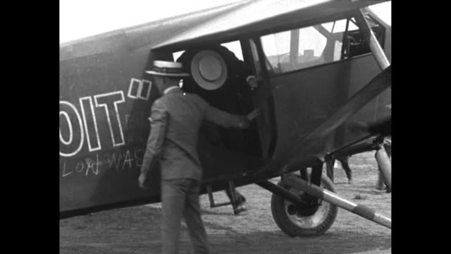 vídeos de stock, filmes e b-roll de men walk alongside the pride of detroit airplane at the opening of the transcontinental airport of toledo / a large crowd at a hangar / edward schlee... - uniforme militar