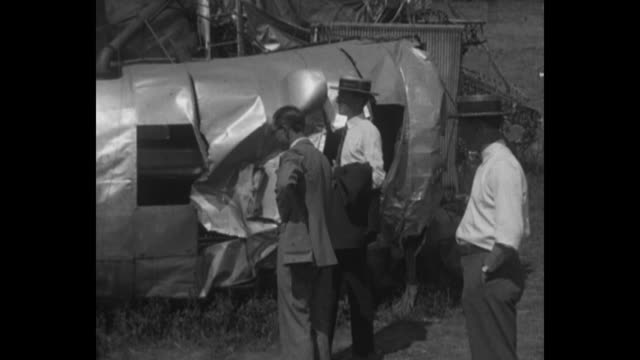 men walk down a steep hill to the massive wreckage of the uss shenandoah / lieutenant charles e. bauch and other military men talk with a civilian... - 飛行船点の映像素材/bロール