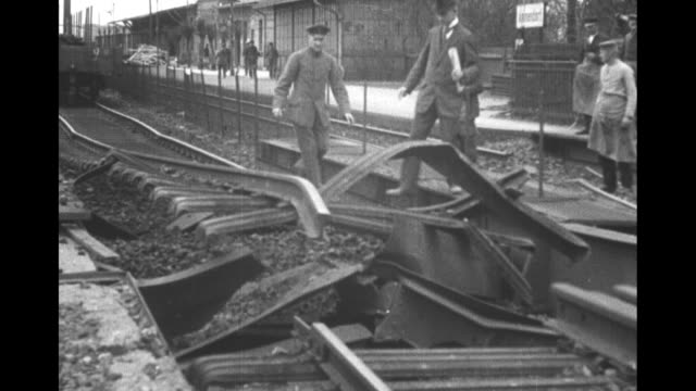 stockvideo's en b-roll-footage met men walk on the rails of a track twisted by an explosion people stand atop railroad cars blown over by the explosion and men cluster at another... - 1921