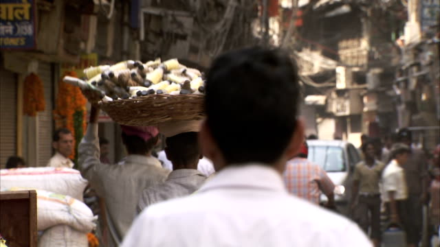 men walk through a market carrying wide baskets on their heads. - delhi stock videos & royalty-free footage