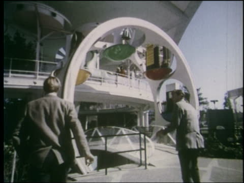 view 2 men walk under rotating display at entrance to building at ny world's fair - esposizione universale di new york video stock e b–roll
