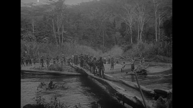 vs men walking across a hollow log over water as nude soldiers wash beyond others crossing a log with two of them carrying a litter / vs as two men... - carrying pole stock videos & royalty-free footage