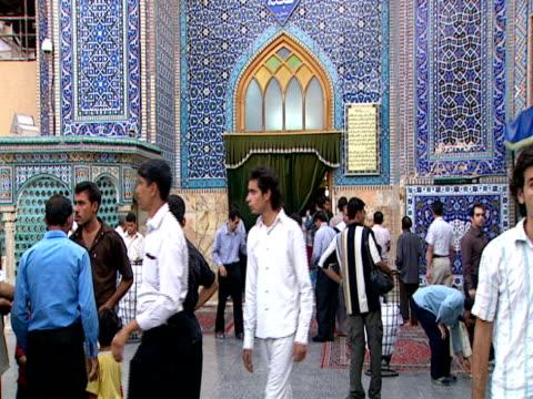 men walking around qom shrine while muslim elder sings an arabic prayer / qom, iran - letterbox format stock videos & royalty-free footage