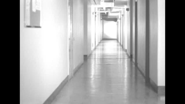 vidéos et rushes de men walking away from camera, pushing dolly with newsreels down corridor turning corner / empty corridor / men with dolly walking toward camera... - boîte de film