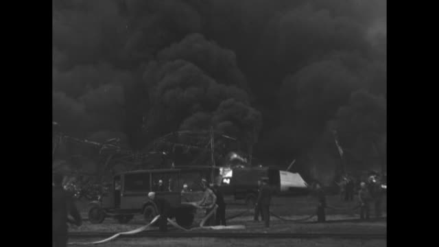 men walking back and forth next to burning wreckage / wider shot of burning wreckage men pulling fire hose out of back of truck next to wreckage /... - airship stock videos & royalty-free footage