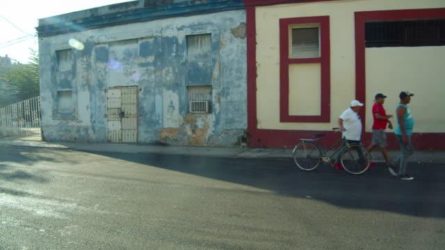 vídeos y material grabado en eventos de stock de men walking down a street in the shadow of a run-down building in havana, cuba - pared de cemento