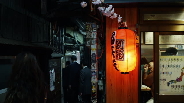 men walking down narrow passage off yakitori alley, tokyo - 居酒屋点の映像素材/bロール