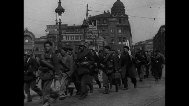 stockvideo's en b-roll-footage met men walking down street. billboard propaganda for enlistment. vs munitions factory soviet tank turret workers. ext vs madrid soldiers walking down... - in dienst gaan