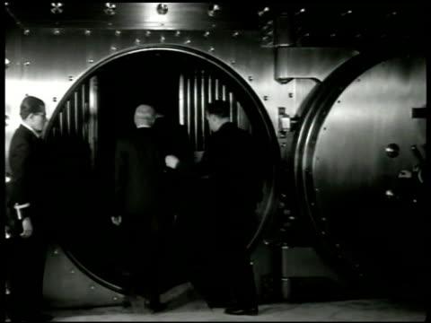 vidéos et rushes de men walking into bank vault one pushing cart int valut men placing sacks of money on shelves cu man stacking numbered sacks franco regime wwii - activité bancaire