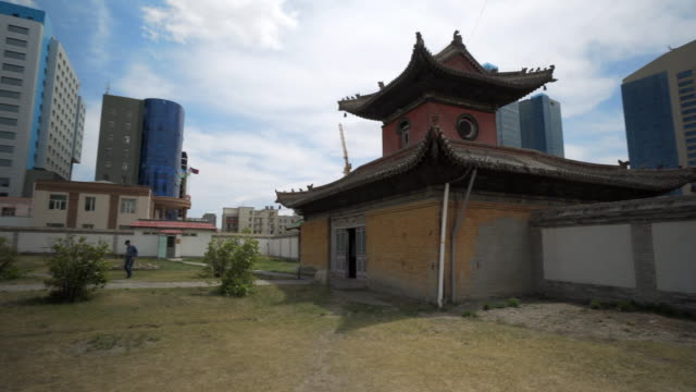 vídeos de stock e filmes b-roll de men walking on field at choijin lama temple in city against sky - ulaanbaatar, mongolia - ulan bator