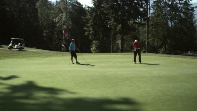 vídeos y material grabado en eventos de stock de ws pan tu men walking on golf course, golf cart in background / squamish, british columbia, canada. - gorra de béisbol