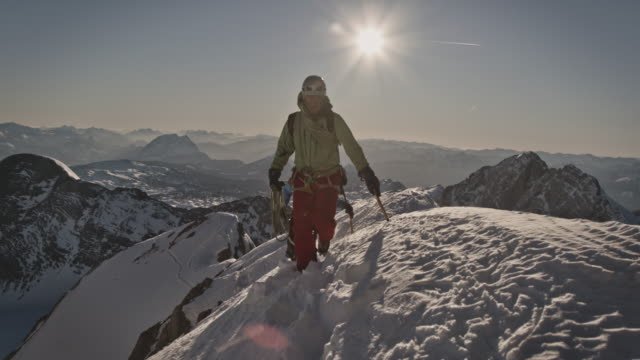 männer, die auf dem kamm des schneebedeckten berges spazieren gehen - bergsteigen stock-videos und b-roll-filmmaterial