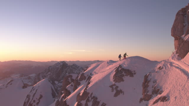 men walking on snow covered ridge at sunrise - snowcapped mountain stock videos & royalty-free footage