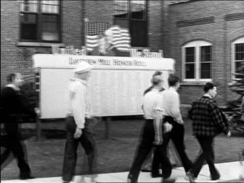b/w 1944 pan men walking past honor roll sign / educational - 戦争記念碑点の映像素材/bロール