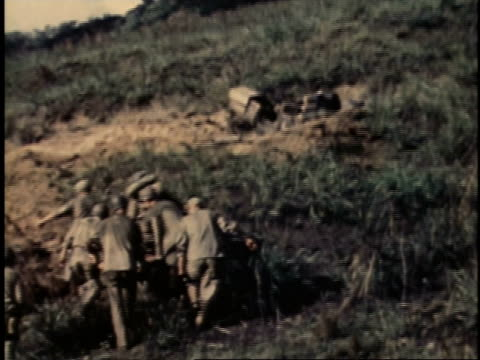 men walking through field and up a hill carrying an injured man on a stretcher / guam - guam stock videos & royalty-free footage