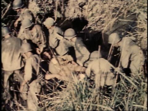 men walking through field carrying an injured man on a stretcher / guam - guam stock videos & royalty-free footage