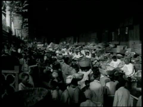 vidéos et rushes de men walking through hindu bazaar w/ raised tarp store fronts ls crowded produce market by building w/ people walking w/ large baskets on heads ms... - 1942