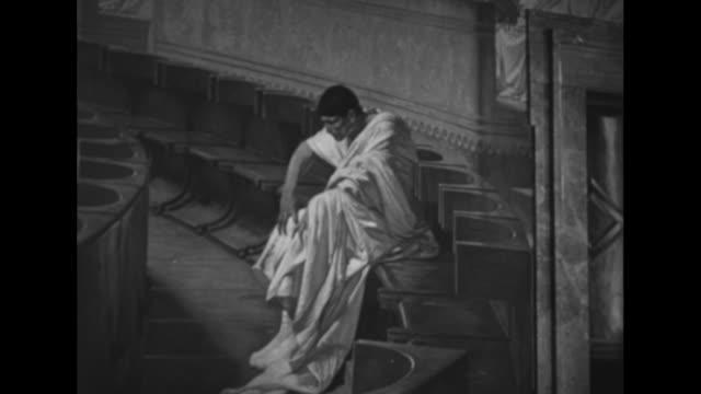 Men walking through Maccari Hall at the Palazzo Madama looking at wall murals of ancient Roman statesmen / pan mural 'Cicero Denounces Catiline' by...