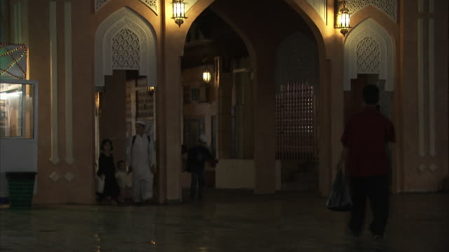 ms men walking through traditional archways on end of  cross street or alley / muscat, oman - vicolo video stock e b–roll