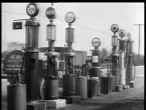 b/w 1927 2 men walking to row of gas pumps at rural service station / educational - ölindustrie stock-videos und b-roll-filmmaterial
