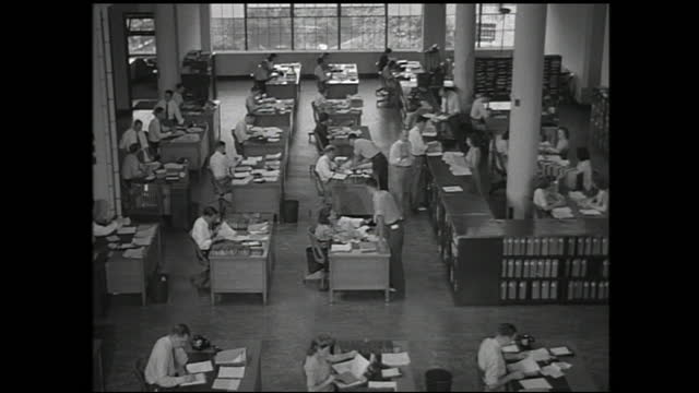 men walking toward building; floor full of people working behind office desks and men distributing paperworks - 1940 1949 video stock e b–roll