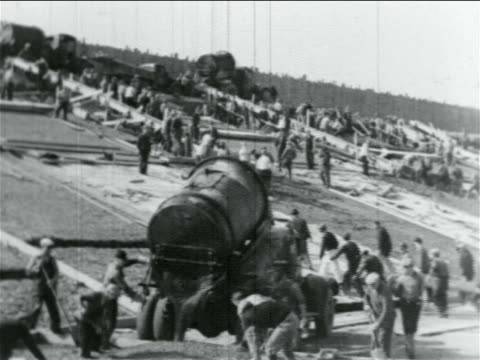 b/w 1934 men walking up hill past concrete pouring in wpa construction project / documentary - new deal video stock e b–roll