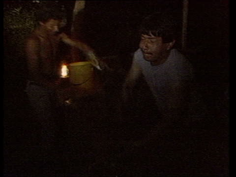 stockvideo's en b-roll-footage met men walking with flashlights on coca plantation/ ms man pulling chicken out of bag and killing it/ ms women plucking chicken/ms man arriving with... - cowboyhoed