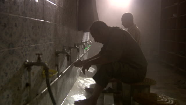 men wash in a communal sink in a bathhouse. - bathhouse stock videos & royalty-free footage