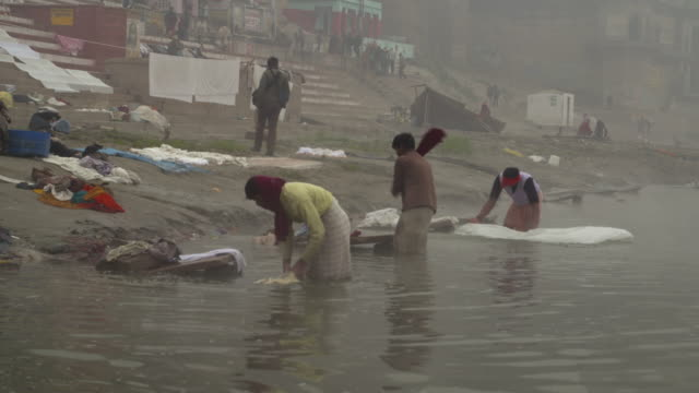 Men washing clothes in the banks of Ganges