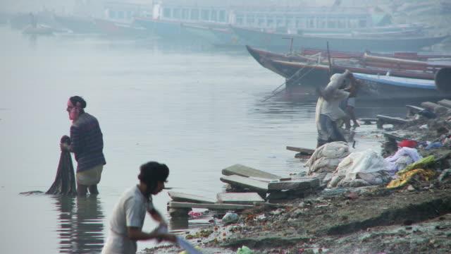 men washing laundry in river - dhoti video stock e b–roll
